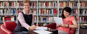 Jill Yates-Wolff and a student sitting in the Rheinbach library.
